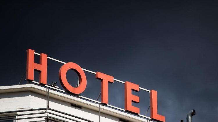 Dunkle Wolken ziehen über einem Hotel hinweg. Foto: Christoph Schmidt/dpa/Symbolbild