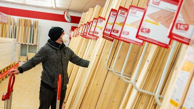 Kunde Timo kauft in der Holzabteilung eines Baumarktes ein. Foto: Nicolas Armer/dpa