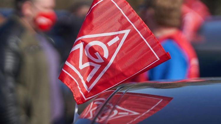 Eine Fahne der IG Metall hängt an einem Auto. Foto: Thomas Frey/dpa