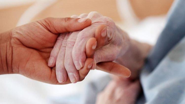 Eine Pflegerin hält die Hand einer älteren Dame. Foto: Oliver Berg/dpa/Archivbild
