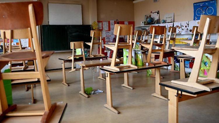 Stühle sind in einem Klassenzimmer hochgestellt. Foto: Britta Pedersen/dpa-Zentralbild/dpa