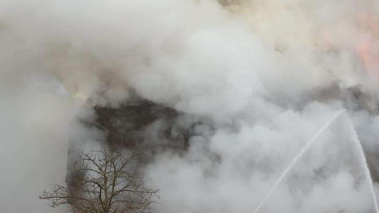 Einsatzkräfte der Feuerwehr löschen ein brennendes Reetdachgebäude. Foto: Ingo Hüttmann/Kreisfeuerwehrverband Rendsburg-Eckernförde/dpa
