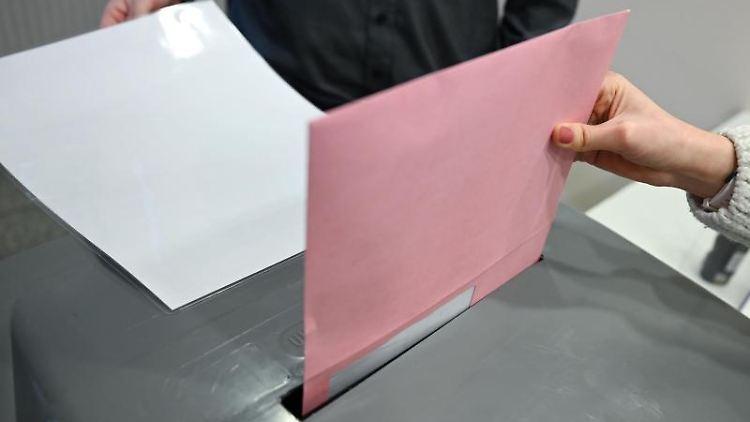 Ein Umschlag mit Briefwahlunterlagen wird im Briefwahllokal in eine Wahlurne geworfen. Foto: Arne Dedert/dpa
