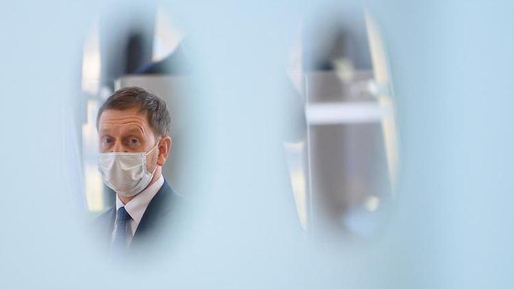 Michael Kretschmer (CDU), Ministerpräsident von Sachsen sitzt hinter einer Eingangstür. Foto: Robert Michael/dpa-Zentralbild/dpa