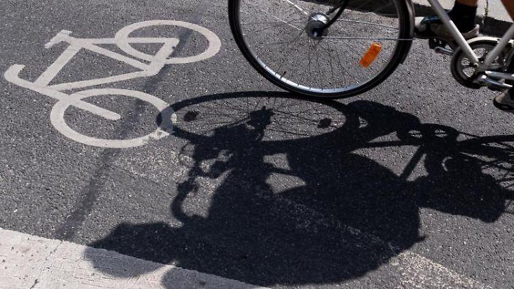 Ein Radfahrer wirft einen Schatten auf einem ausgewiesenen Radweg. Foto: Peter Kneffel/dpa/Symbolbild