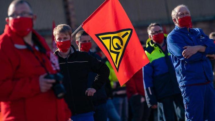Streikende mit einer Fahne der IG-Metall stehen auf einer Straße. Foto: Nicolas Armer/dpa