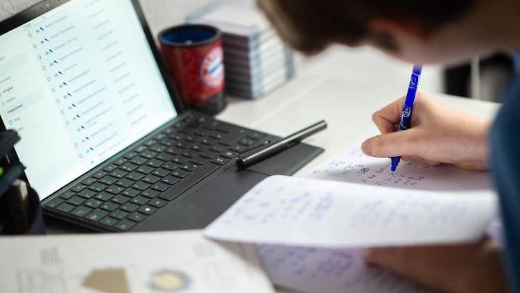 Ein Schüler sitzt in seinem Zimmer am Schreibtisch und erledigt Aufgaben im Rahmen des Homeschoolings. Foto: Jonas Güttler/dpa