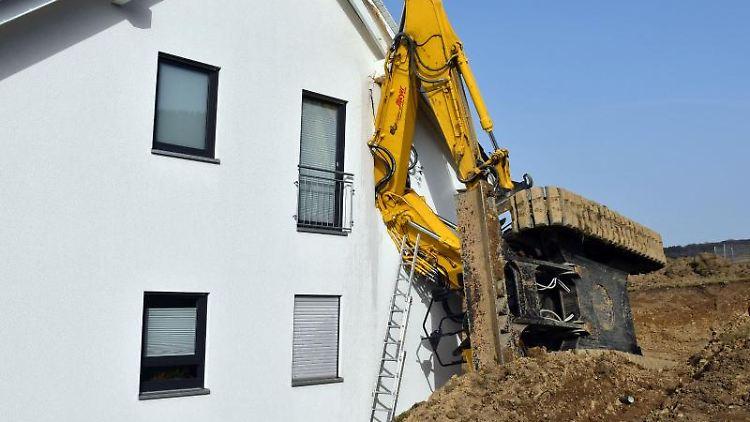 Der Bagger lehnt an der Außenwand des Neubaus in Burbach. Foto: Jürgen Schade/dpa