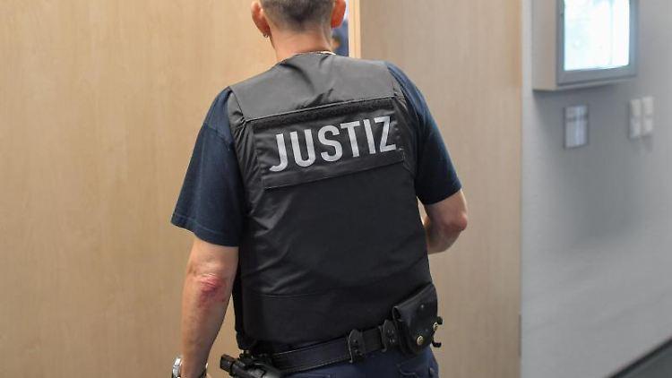 Ein Justizmitarbeiter schließt die Tür zu einem Verhandlungssaal. Foto: Patrick Pleul/zb/dpa/Symbolbild