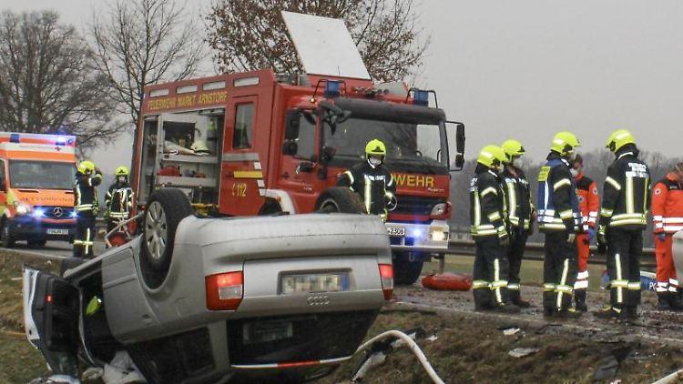 Rettungskräfte stehen am Unfallort an den Wracks von zwei Autos. Foto: -/Zema-Medien/dpa