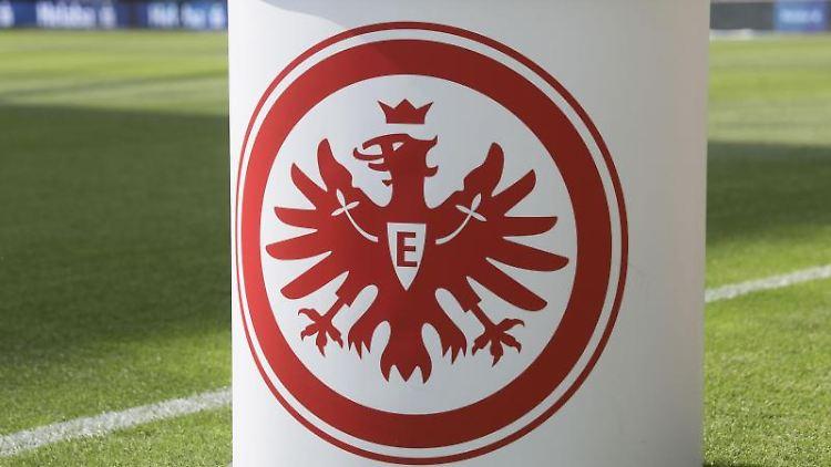 Das Logo von Eintracht Frankfurt ist auf einem Pult zu sehen. Foto: Frank Rumpenhorst/dpa/Archivbild