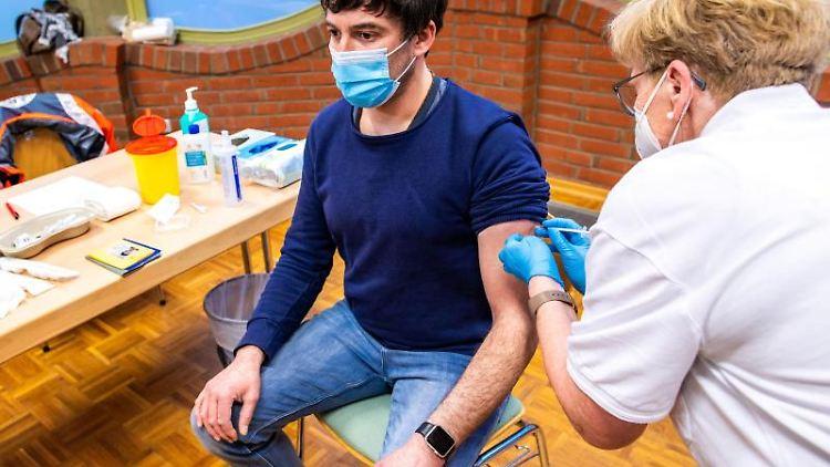 Der Sportlehrer Rene Kirstein wird von Krankenschwester Susanne Kugel gegen Corona geimpft. Foto: Jens Büttner/dpa-Zentralbild/dpa
