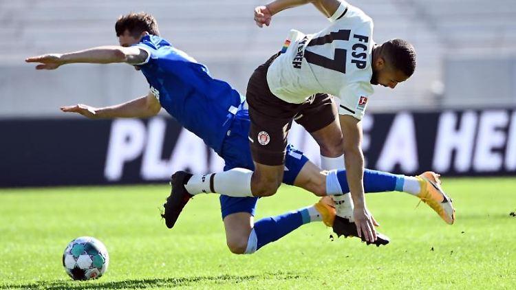 Der Karlsruher Philip Heise und Paulis Daniel-Kofi Kyereh (l-r.) kämpfen um den Ball. Foto: Uli Deck/dpa