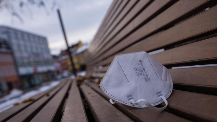 Eine FFP2-Maske liegt auf einer Parkbank in Schweinfurt. Foto: Nicolas Armer/dpa/Archivbild