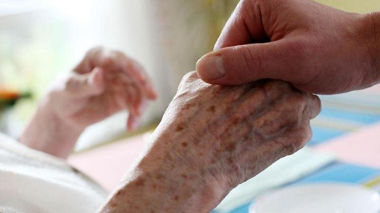Ein Pfleger hält in einem Alten- und Pflegeheim die Hand einer Bewohnerin. Foto: picture alliance/dpa/Symbolbild