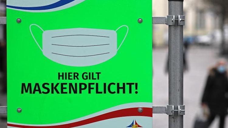 Auf dem Fußgänger-Boulevard Breite Straße in Rostock weist ein Schild auf die Maskenpflicht hin. Foto: Bernd Wüstneck/dpa-Zentralbild/dpa/Archivbild