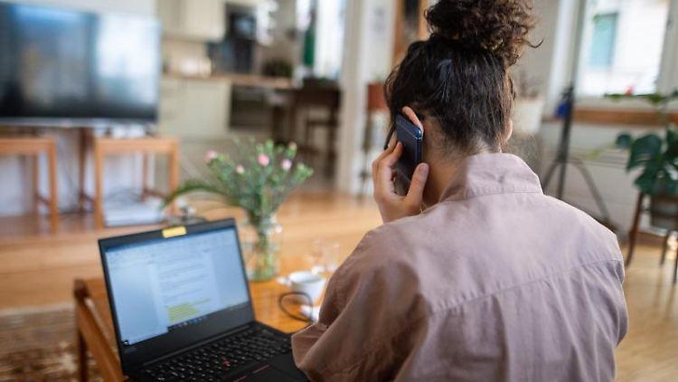 Eine Frau nimmt im Homeoffice aus ihrem Wohnzimmer an einer Telefonkonferenz teil. Foto: Sebastian Gollnow/dpa/Archivbild