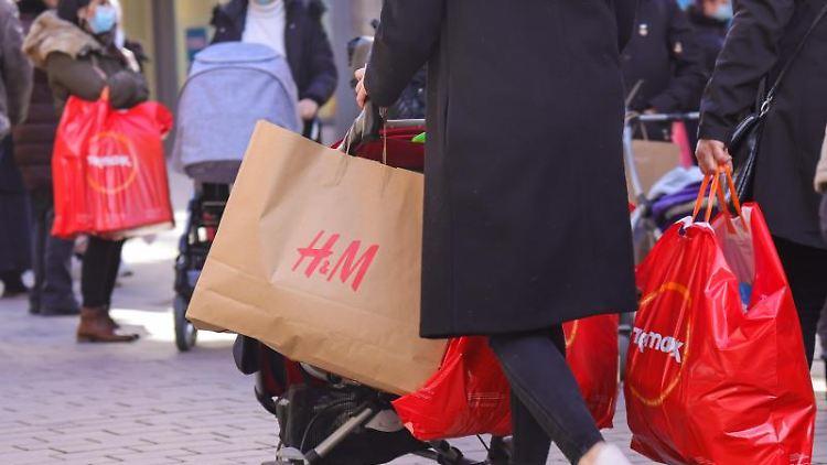 Kundinnen tragen ihre Einkaufstüten durch die Innenstadt. Foto: Ulrich Perrey/dpa