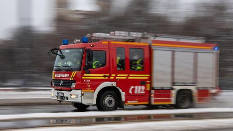 Ein Feuerwehrwagen fährt mit Blaulicht durch die Innenstadt. Foto: Peter Kneffel/dpa/Symbolbild