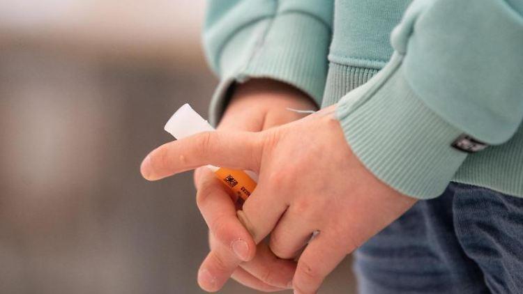 Eine Schülerin hält während eines selbst durchgeführten Corona-Tests ihr Teströhrchen mit einer Speichelprobe. Foto: Matthias Balk/dpa/Symbolbild