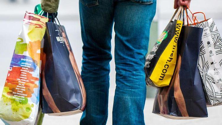 Ein Mann trägt Tragetaschen mit Einkäufen. Foto: picture alliance/Hauke-Christian Dittrich/dpa/Symbolbild