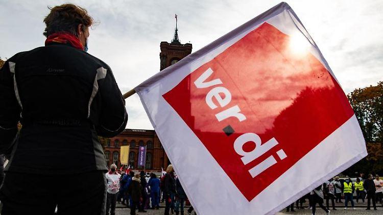 Eine Frau hält am Roten Rathaus eine Fahne mit dem Logo der Gewerkschaft Verdi in den Händen. Foto: Paul Zinken/dpa/Archivbild