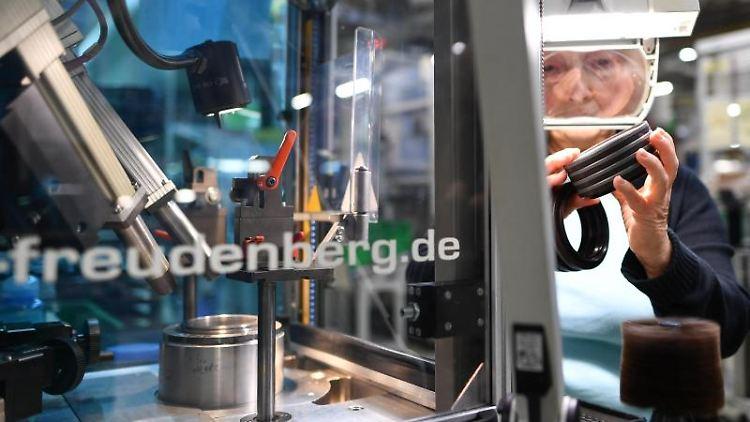 Ein Mitarbeiterin kontrolliert in einem Fabrikgebäude des Technologiekonzerns Freudenberg Dichtungsringe. Foto: picture alliance / Uwe Anspach/dpa/Archivbild