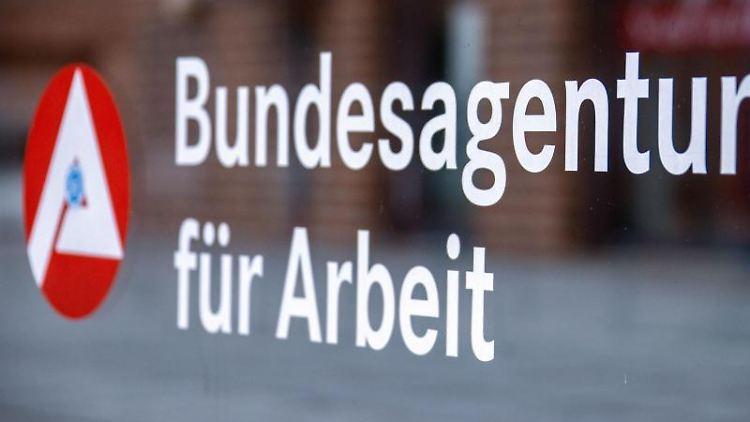 Das Hinweisschild für die Bundesagentur für Arbeit ist an einer Glasfläche vor einem Bürogebäude zu sehen. Foto: Jens Büttner/dpa-Zentralbild/dpa/Symbolbild