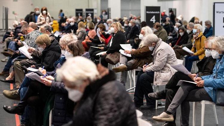 Menschen warten mit Mund-Nasen-Bedeckung in einem Impfzentrum. Foto: Marius Becker/dpa