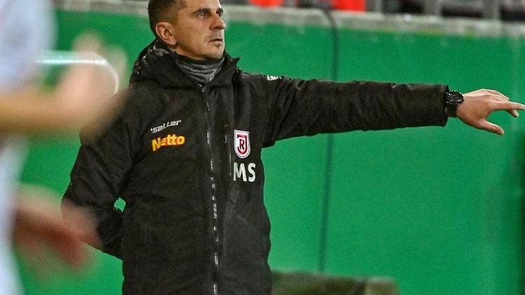 Trainer Mersad Selimbegovic von Regensburg steht am Spielfeldrand. Foto: Armin Weigel/dpa/archivbild