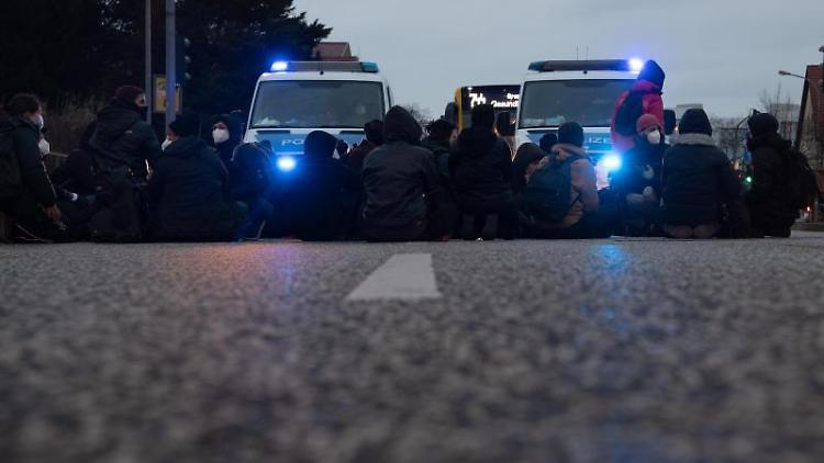 Demonstranten blockieren eine Kreuzung auf der Waßmannsdorfer Chaussee in Schönefeld. Foto: Paul Zinken/dpa-Zentralbild/dpa