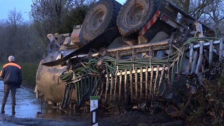 Nach einem Unfall liegt ein Traktor mit geladener Gülle auf dem Dach. Foto: Tebben/NWM-TV/dpa