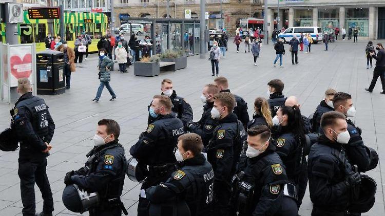 Polizisten auf dem Marktplatz in Halle, nachdem die Versammlungen in Leipzig untersagt worden sind. Foto: Sebastian Willnow/dpa-Zentralbild/dpa
