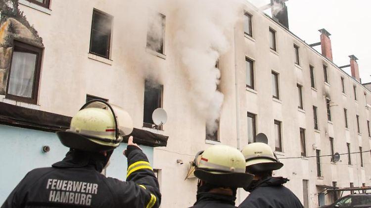 Feuerwehrleute stehen im Stadtteil Billstedt vor einer brennenden Wohnung. Foto: Daniel Bockwoldt/dpa