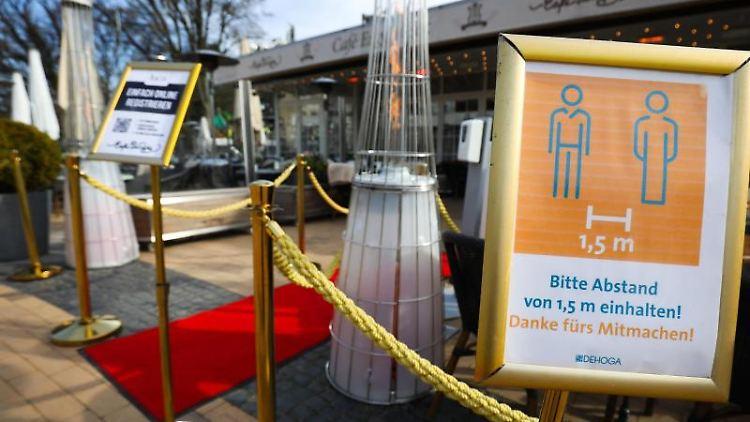 Schilder zum Gebot des Abstandhaltens (r) und zur Luca-App stehen am Eingang der Außenterasse des Cafes