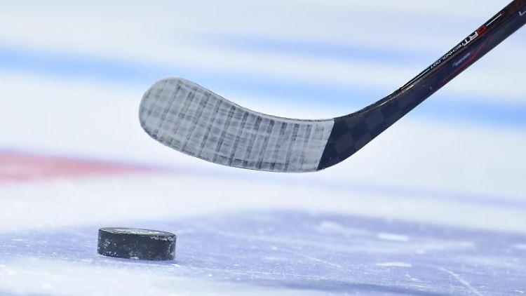Puck und Schläger bei einem Eishockey-Spiel. Foto: Uwe Anspach/dpa/Symbolbild