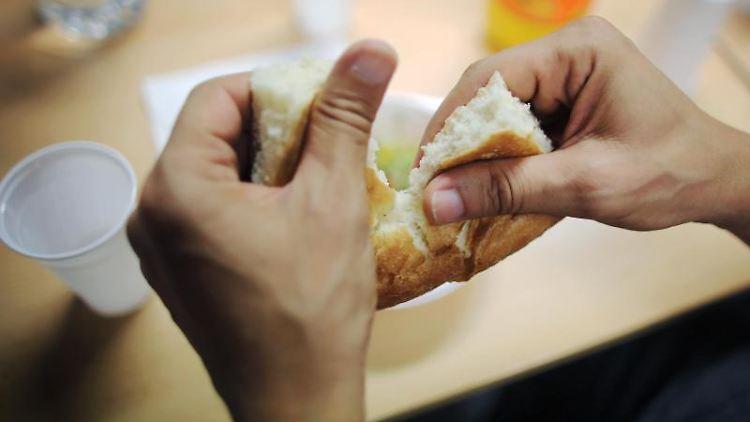Ein Mann bricht ein Brot. Foto: Fredrik von Erichsen/dpa/Archivbild