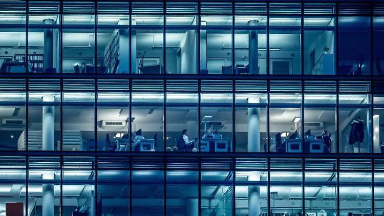 Wenige Menschen arbeiten am späten Nachmittag in einem Bürogebäude. Foto: Michael Kappeler/dpa/Archivbild