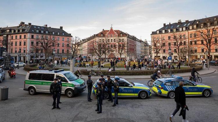 Polizisten stehen am Gärtnerplatz im Herzen der Stadt, während Passanten auf dem Platz verweilen. Foto: Peter Kneffel/dpa/Archivbild