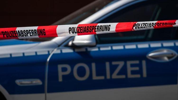 Ein Polizeiauto steht hinter einem Absperrband der Polizei. Foto: Robert Michael/dpa-Zentralbild/dpa/Archivbild