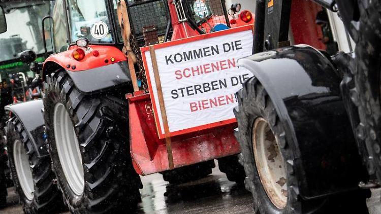 Landwirte nehmen mit Traktoren an einer Demonstration gegen den Brenner-Nordzulauf teil, während an einem Schlepper ein Schild mit der Aufschrift
