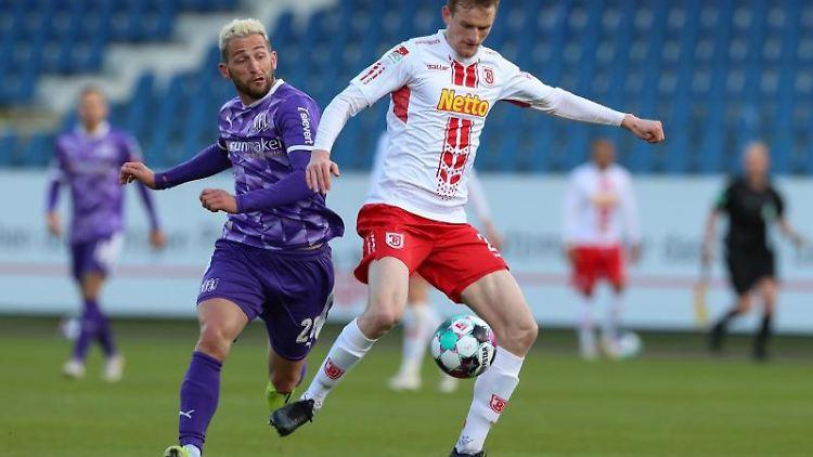 Osnabrücks Marc Heider (l) im Kampf um den Ball mit Regensburgs Scott Kennedy. Foto: Friso Gentsch/dpa