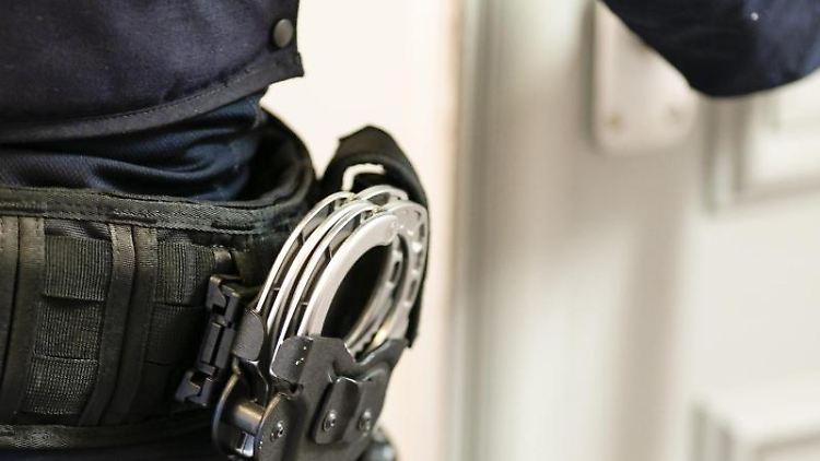 Handschellen sind an einem Gürtel eines Beamten befestigt. Foto: Frank Molter/dpa/Symbolbild