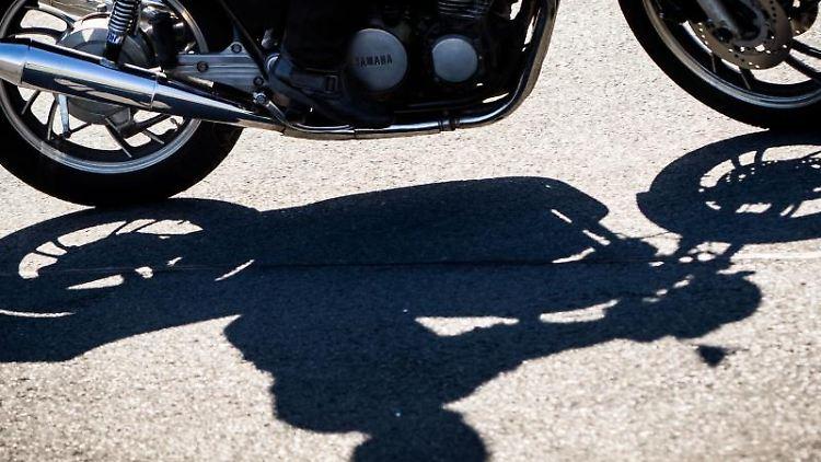 Ein Motorradfahrer und seine Maschine werfen Schatten auf den Asphalt. Foto: Frank Rumpenhorst/dpa/Archivbild