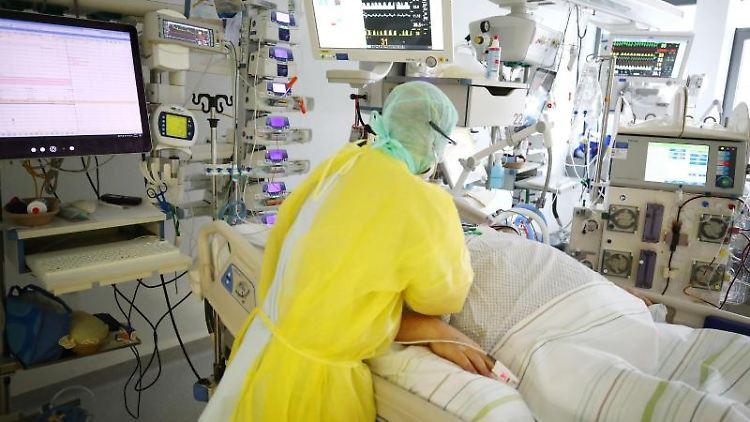 Ein Arzt untersucht einen Patienten auf der Covid-19-Intensivstation im SRH Waldklinikum in Gera. Foto: Bodo Schackow/dpa-zentralbild/dpa