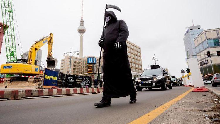 Ein Teilnehmer im Sensenmann-Kostüm läuft bei einem Autokorso von Berliner Polizisten um auf die sogenannte Schießstandaffäre aufmerksam zu machen mit. Foto: Christoph Soeder/dpa