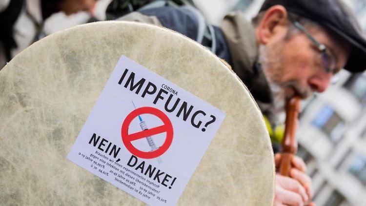 Ein Mann spielt bei einer Demo gegen Corona-Maßnahmen in Berlin Flöte. Foto: Christoph Soeder/dpa/Archivbild