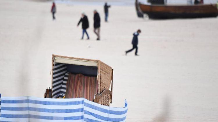 Spaziergänger sind an einem Strand auf Usedom unterwegs. Foto: Stefan Sauer/dpa-Zentralbild/dpa/Archivbild