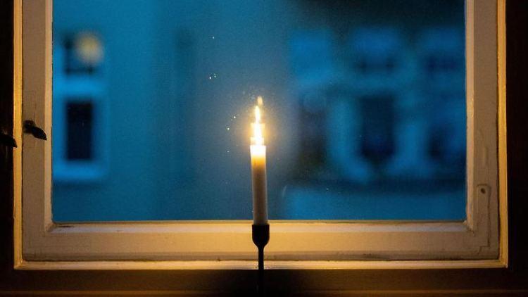 Eine Kerze brennt in einem Fenster als Zeichen des gemeinsamen Gedenkens im Rahmen der Aktion