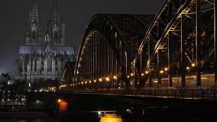 Der Dom und die Hohenzollernbrücke werden abends angestrahlt. Foto: Oliver Berg/dpa/Symbolbild